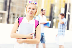 Pretty student standing and smiling in the campus Stock Photos