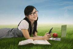Pretty student studying on grass Royalty Free Stock Photos