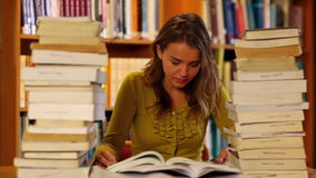 Pretty student studying in the library surrounded by books stock video footage