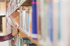 Pretty student taking book out of shelf Royalty Free Stock Photos