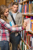 Pretty student taking book from shelf in library Stock Photo