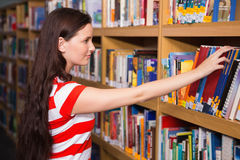 Pretty student taking book from shelf in library Royalty Free Stock Photos