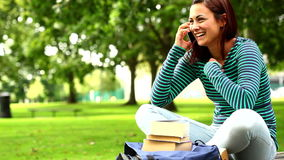 Pretty student talking on phone on the grass stock video