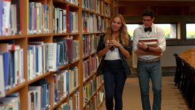 Pretty student talking to nerd in library. At the college stock footage