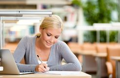 Pretty student working at the desk Stock Image
