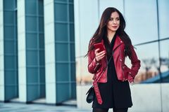 Pretty styilish woman in red jacket is standing next to glass building and chating with someone by mobile phone.  royalty free stock photos