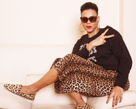Pretty stylish african american big mama woman well dressed. swag relax at home, leopard print on clothers. Fashion look stock photos