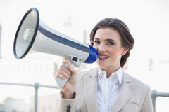 Pretty stylish brown haired businesswoman holding a megaphone Stock Photography