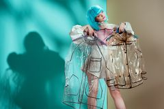 Pretty stylish girl in blue wig holding hangers. With transparent raincoats royalty free stock photo