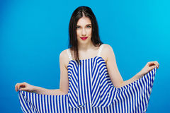 Pretty stylish girl with long hair wearing classy beautiful blue dress and posing against blue background. Fashion vogue Royalty Free Stock Images