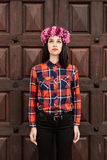 Pretty stylish girl with pink flower crown in front of a wooden Stock Photography