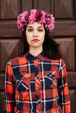 Pretty stylish girl with pink flower crown in front of a wooden Royalty Free Stock Photos