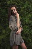 Pretty stylish model in long shirt posing on a green tree backgr Royalty Free Stock Photos