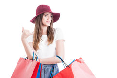 Pretty stylish shopaholic doing a calling gesture with hand Stock Photo