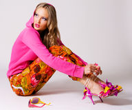 Pretty stylish woman in colorful clothing. On gray background Royalty Free Stock Photos