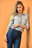 Pretty stylish woman in denim shirt and jeans posing outdoors. Royalty Free Stock Images