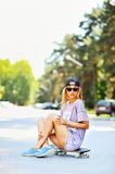 Pretty stylish woman sitting on skateboard Stock Photography