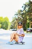 Pretty stylish woman sitting on skateboard Stock Photography