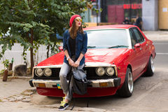 Pretty stylish woman standing by the retro car. Pretty stylish woman standing by the red retro car Royalty Free Stock Images