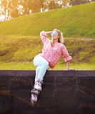 Pretty stylish woman in sunglasses with roller skates in city Royalty Free Stock Photography