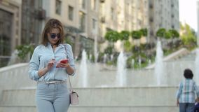 Beautiful elegance woman using phone at fountain background stock footage