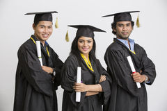 Pretty successful Indian girl college graduate wearing cap and gown holding diploma Royalty Free Stock Images