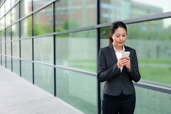 Pretty suit woman standing outdoor sidewalk. Pretty suit rights woman standing outdoor sidewalk corridor using mobile smart phone to texting send messages with stock image