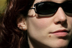 Pretty with sunglasses. A close cropped image of a pretty female with a beauty mark wearing sunglasses stock photo