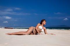 Pretty suntanned girl on white sand. Beautiful girl in bikini sunbathes on a beach with white sand Stock Photography