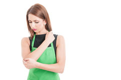 Pretty supermarlet seller with elbow pain Royalty Free Stock Photo