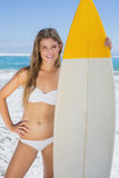 Pretty surfer girl holding her surfboard on the beach Stock Image