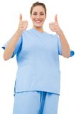 Pretty surgeon in blue scrubs giving thumbs up Royalty Free Stock Images