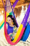 Pretty surprised cheerful young girl on the beach, smiling lies in a hammock against the backdrop of palm trees, lifestyle, tanned stock images