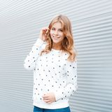 Pretty sweet young woman in a beautiful smile in a trendy sweater stands near a white metal wall in a spring sunny day. European happy girl enjoys a walk royalty free stock images