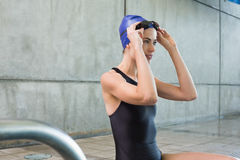 Pretty swimmer sitting at the edge of the swimming pool Royalty Free Stock Images