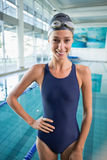 Pretty swimmer standing by the pool smiling at camera Royalty Free Stock Image