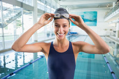 Pretty swimmer standing by the pool smiling at camera Royalty Free Stock Images