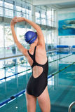 Pretty swimmer stretching by the pool Stock Images