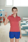 Pretty swimming coach standing poolside at the leisure center Stock Photo