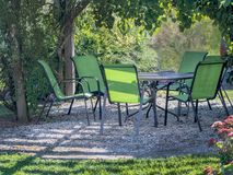 Pretty table and chairs under a green garden arbor stock image