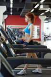 Pretty tall woman exercising on treadmill Royalty Free Stock Image