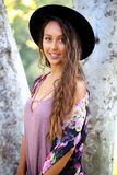 Pretty tan girl in a black hat by a tree Stock Photo