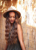 Pretty tan girl in a hat by a bamboo fence Royalty Free Stock Photography