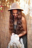 Pretty tan girl in a hat by a bamboo fence petting a dog Stock Image