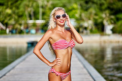 Pretty tanned blonde woman in bikini posing outdoor in summertim Royalty Free Stock Photography