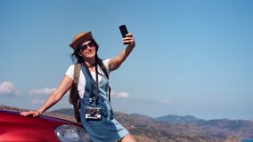 Pretty tanned smiling travel woman enjoying vacation taking selfie using smartphone medium shot