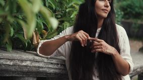 Pretty tanned woman waiting for someone in park with henna tattoos on her hands. A pretty and tanned woman is waiting for someone from her friends in a green stock footage