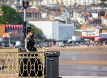 Pretty tattoed gothic young woman on pier royalty free stock images