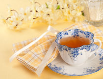 Pretty Tea Cup in Yellow Table Setting. A blue and white teacup with checked napkin on yellow tablecloth with flowers and sugar royalty free stock photography