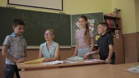 Pretty teacher in classroom sitting at the desk and asking children. education, elementary school, learning and people. Concept stock video